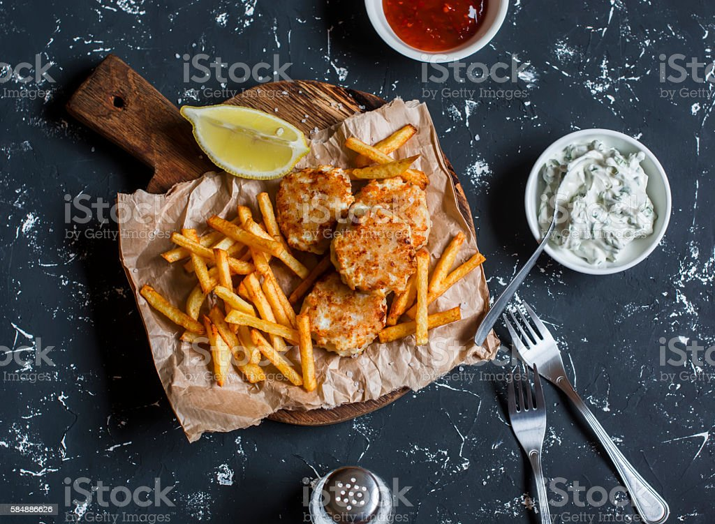 Fish balls, potato chips,  sauces on a dark background stock photo