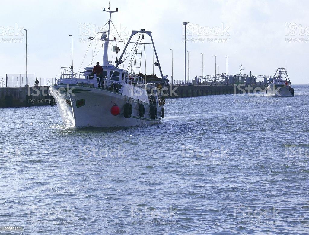 Fish boats return on sunset royalty-free stock photo