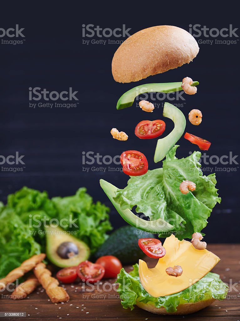 Fish burger with shrimps in motion stock photo