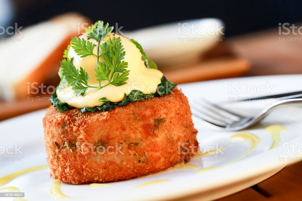 A fish cake with a poached egg and spinach on top stock photo