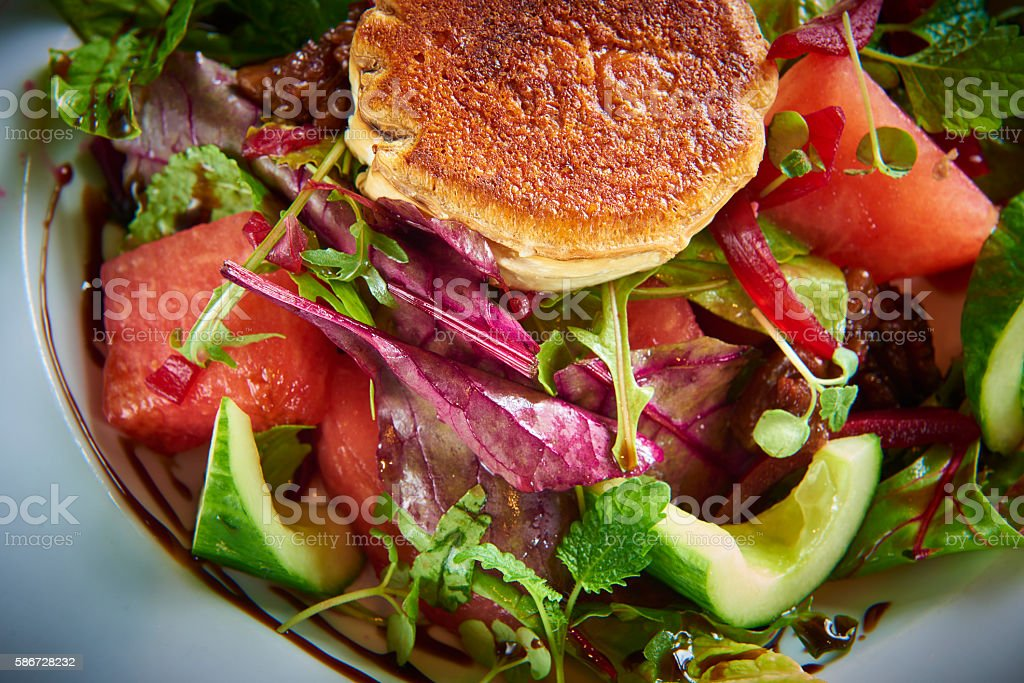 fish cakes garnished with green herbs, salad melon stock photo