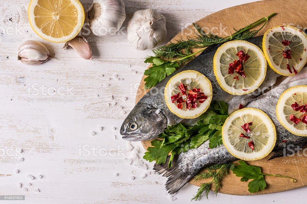 Fish dish cooking with various ingredients. Raw rainbow trout stock photo