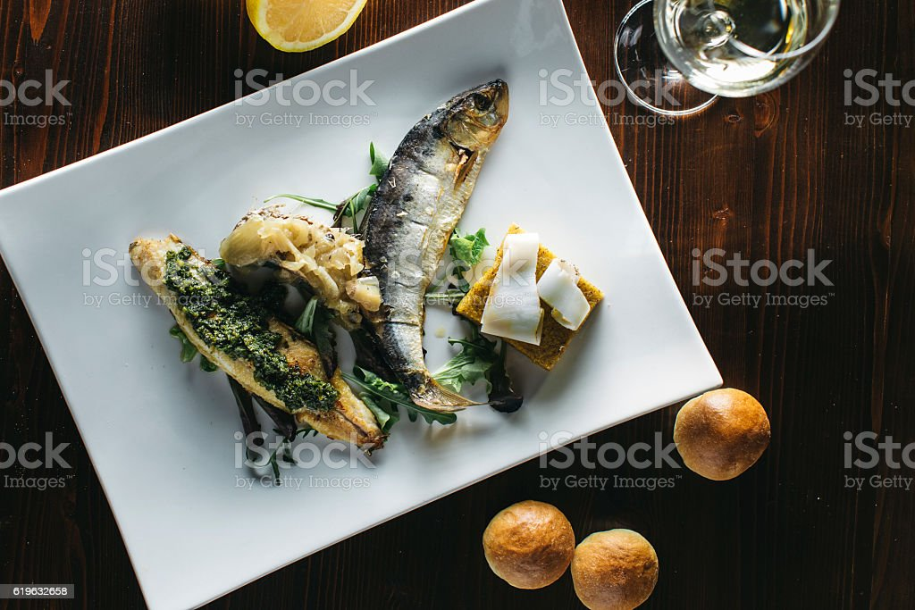 Fish dish with polenta and bacon, traditional Italian cooking stock photo