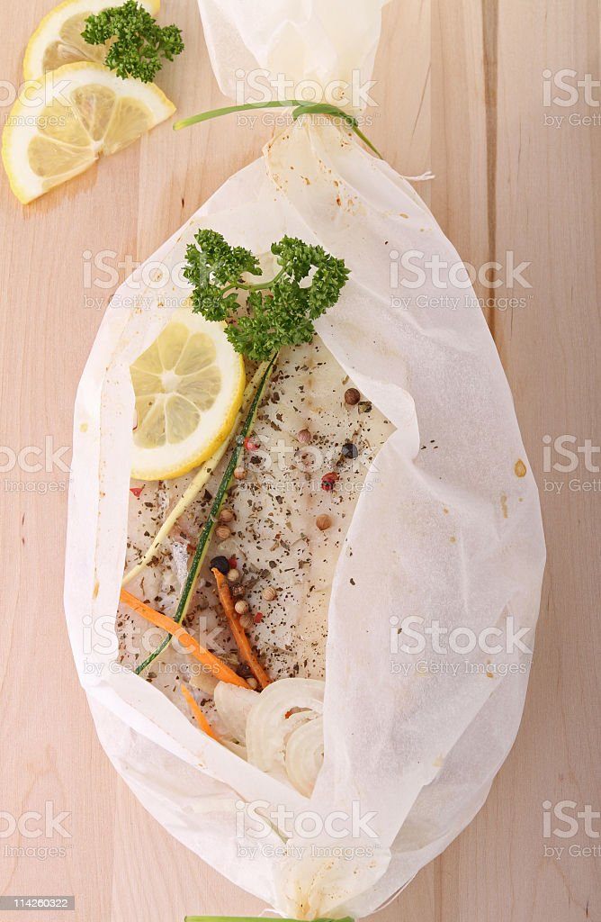 A fish en papillote with lemon wrapped in white plastic  stock photo