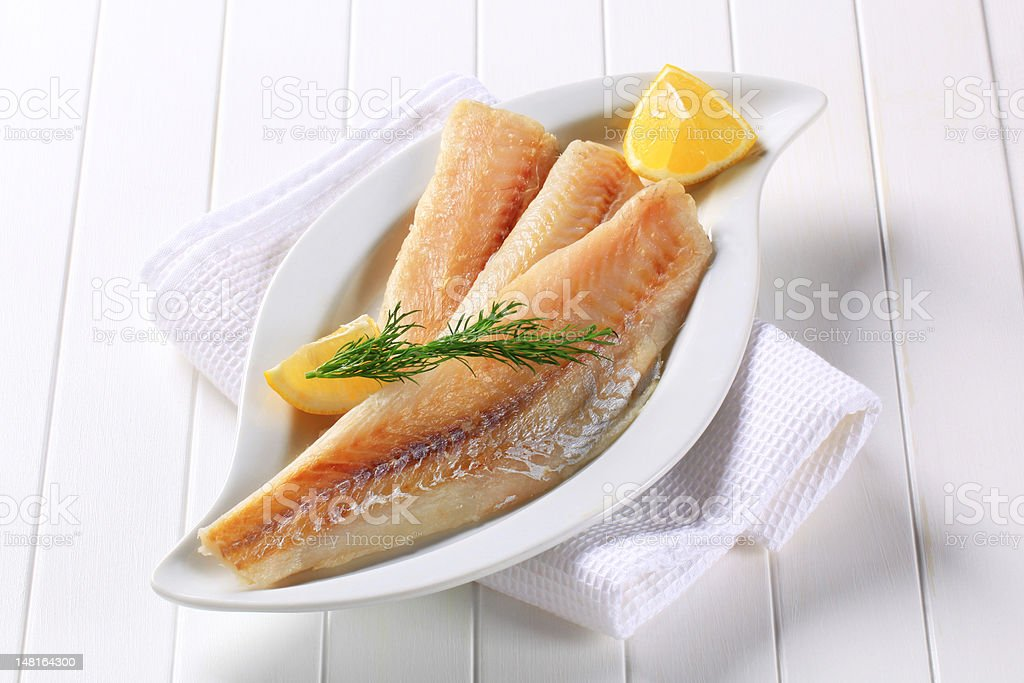 Fish filets displayed on white plate with lemon and herbs stock photo