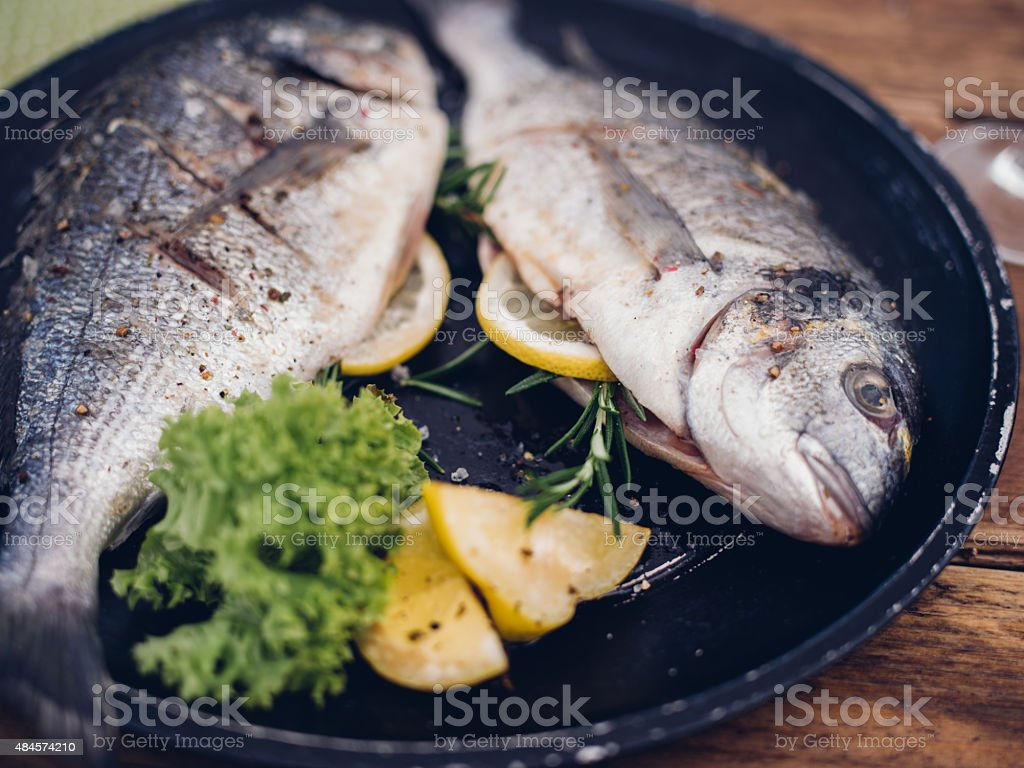 Fish grilled with a stuffing of lemon and rosemary stock photo