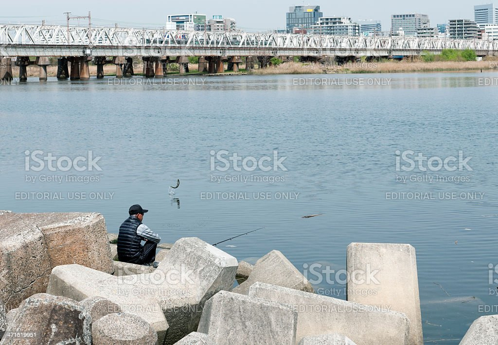 Fish jumping out of river near fisherman in Osaka royalty-free stock photo