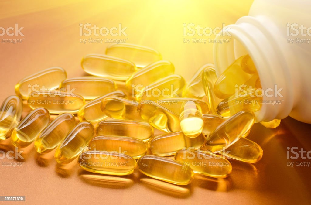 Fish oil and vitamin D softgels stock photo