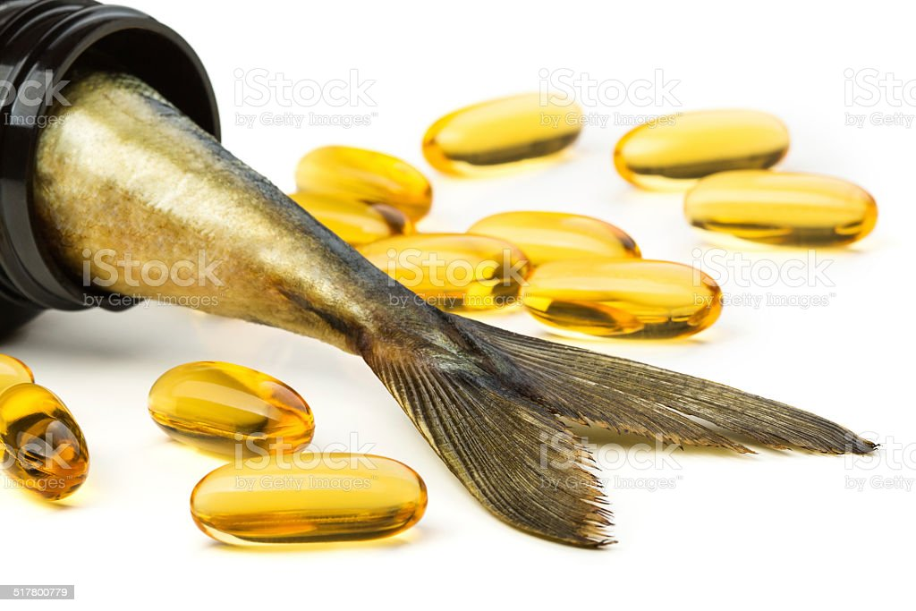 Fish oil capsules and fish tail in brown jar stock photo