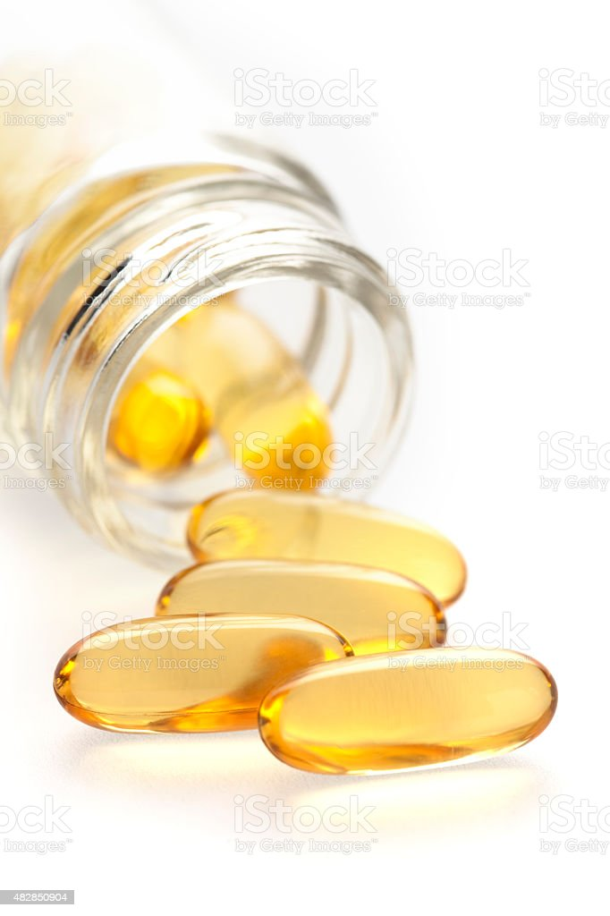 Fish oil capsules coming out of bottle stock photo