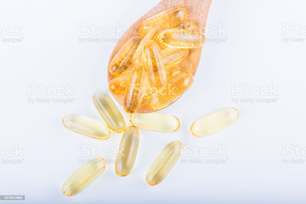 fish oil capsules in a spoon stock photo