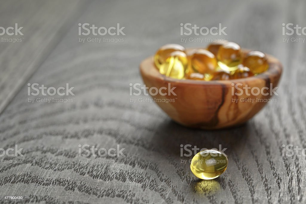 fish oil capsules in wood bowl on wooden table stock photo