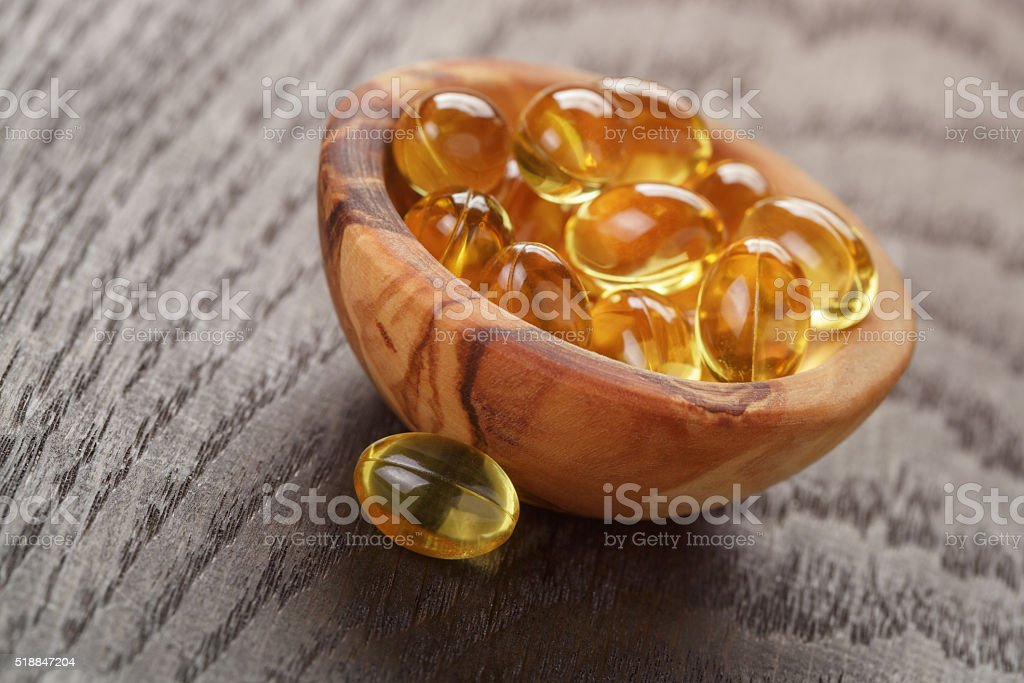 fish oil capsules in wooden bowl on table stock photo