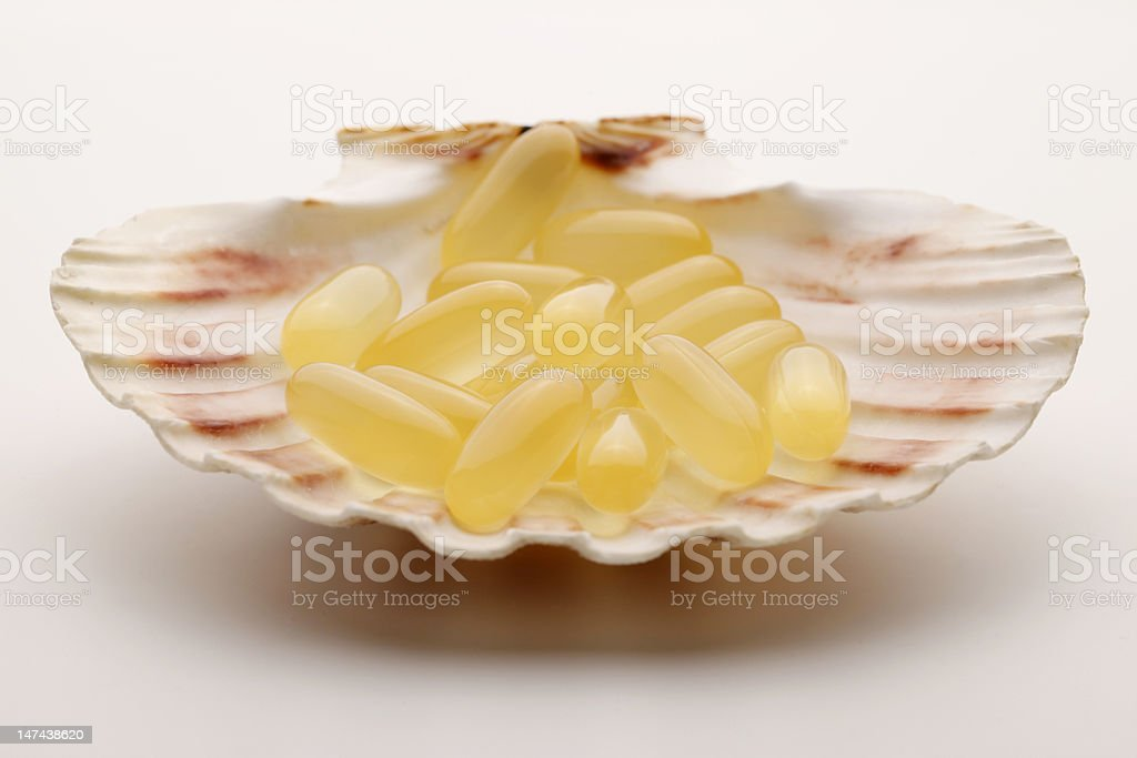 Fish Oil Capsules on a Shell royalty-free stock photo