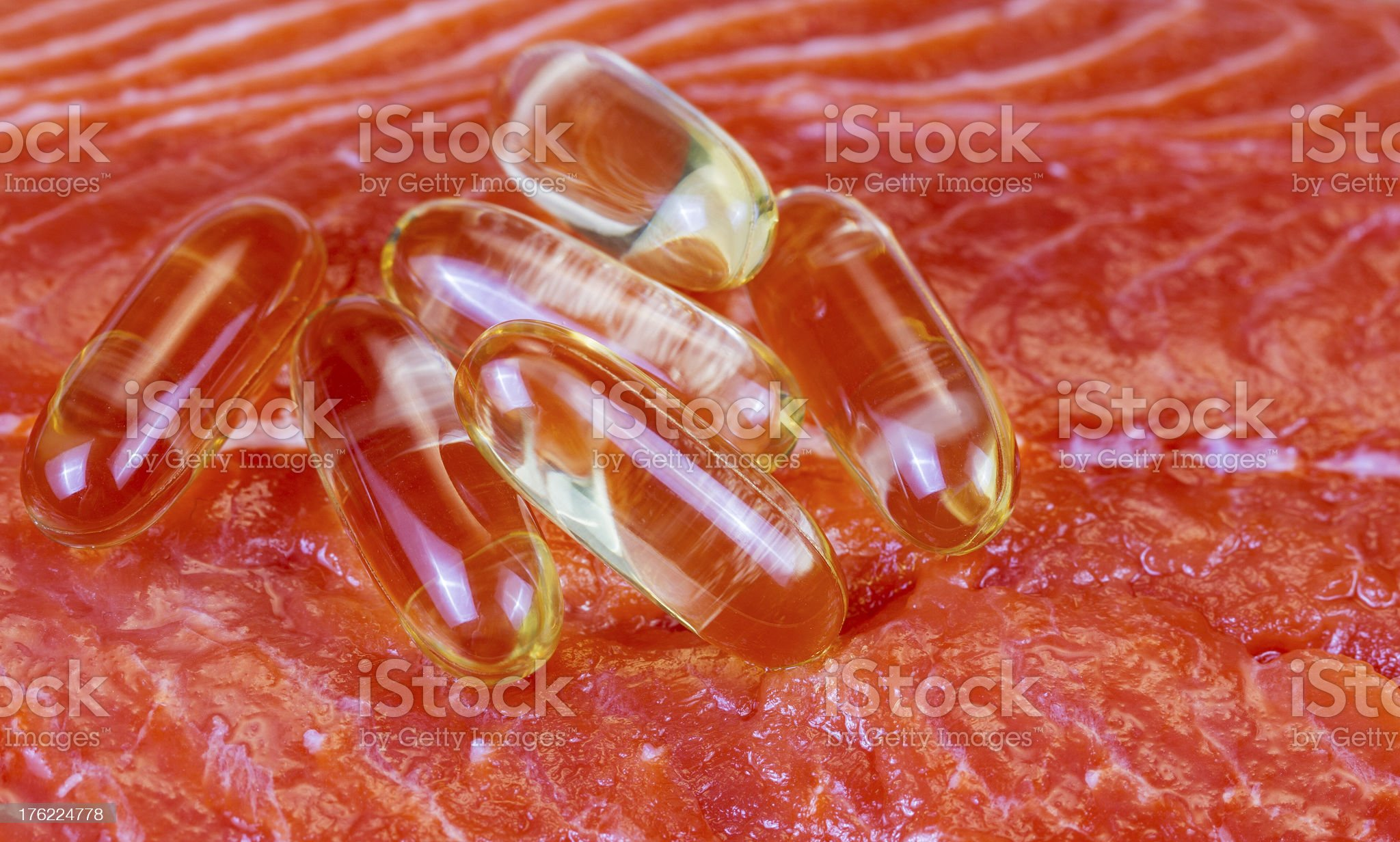 Fish Oil Capsules on Fresh Wild Red Salmon royalty-free stock photo