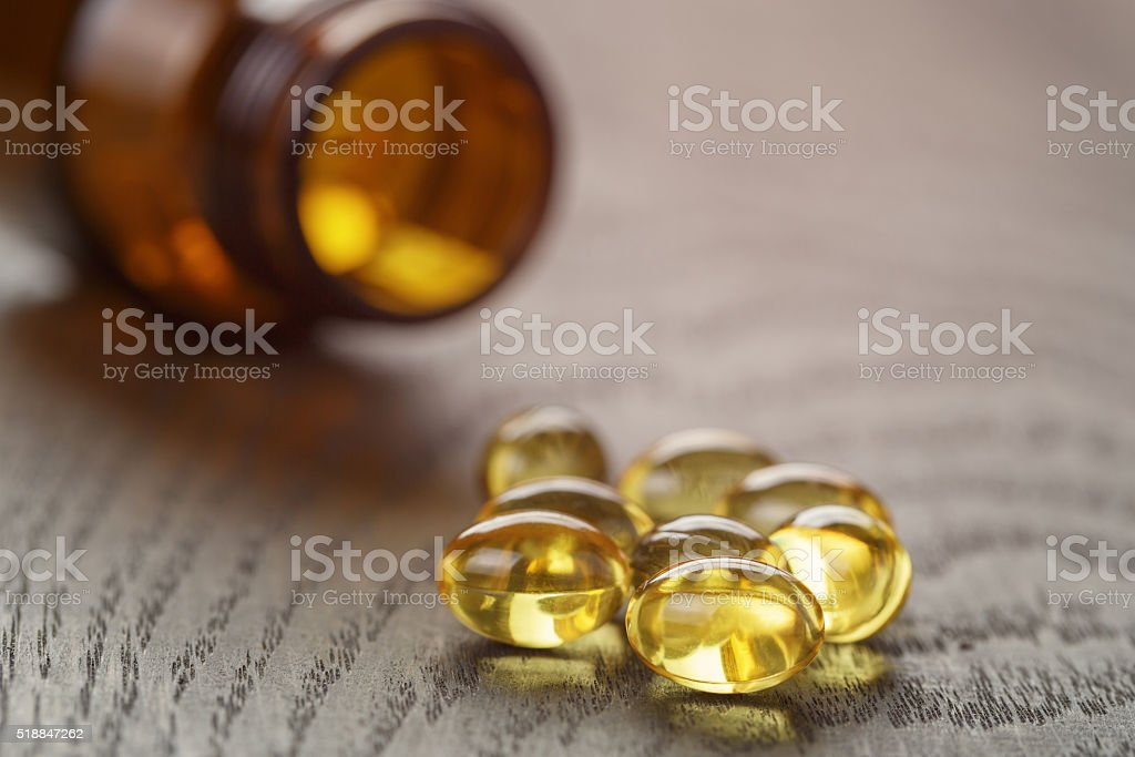 fish oil capsules on wooden tabe stock photo