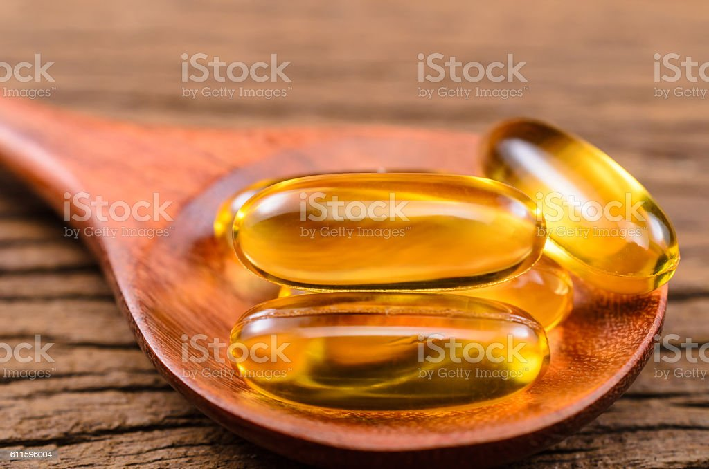 fish oil in wooden spoon stock photo