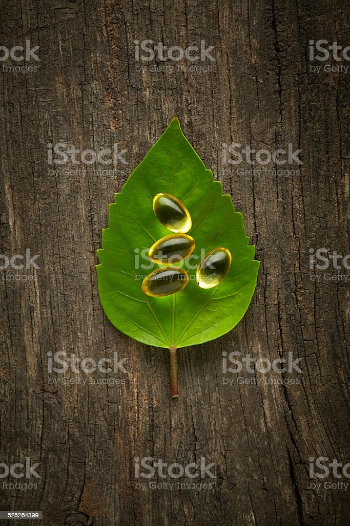 Fish Oil Pills and Green Leaf on a Wooden Table stock photo