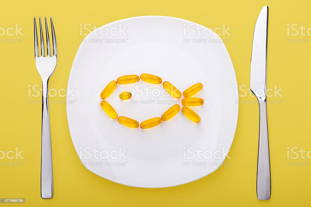fish oil soft gels lying on a plate stock photo