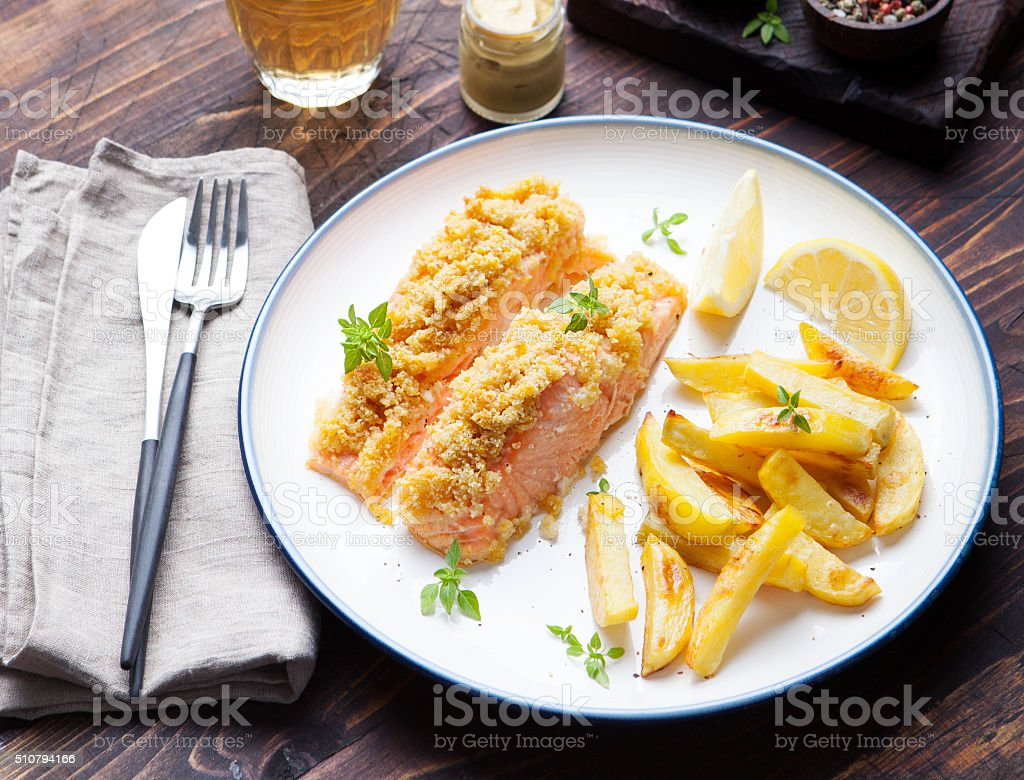 Fish salmon with baked potatoes and lemon slices stock photo