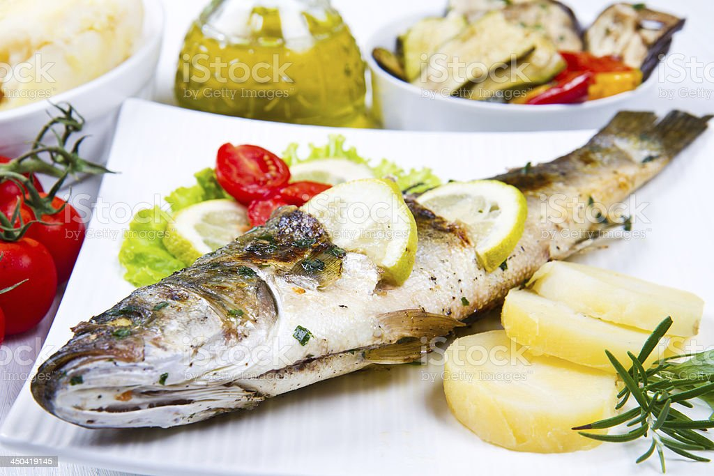 fish, sea bass grilled with lemon and  vegetables stock photo