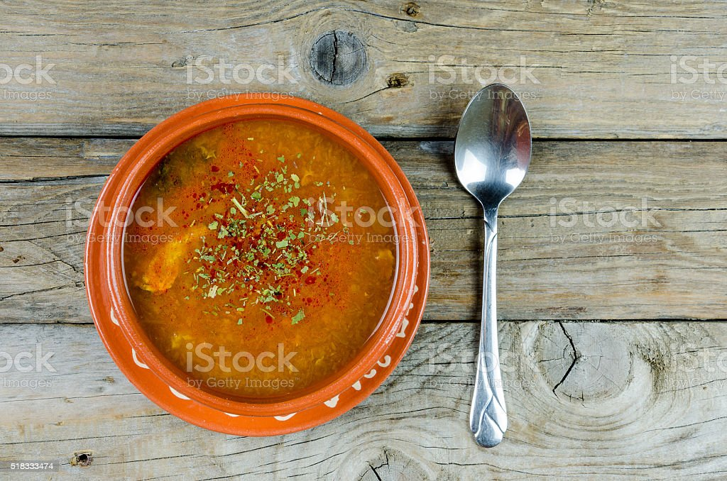 fish soup into a clay plate at board or table stock photo