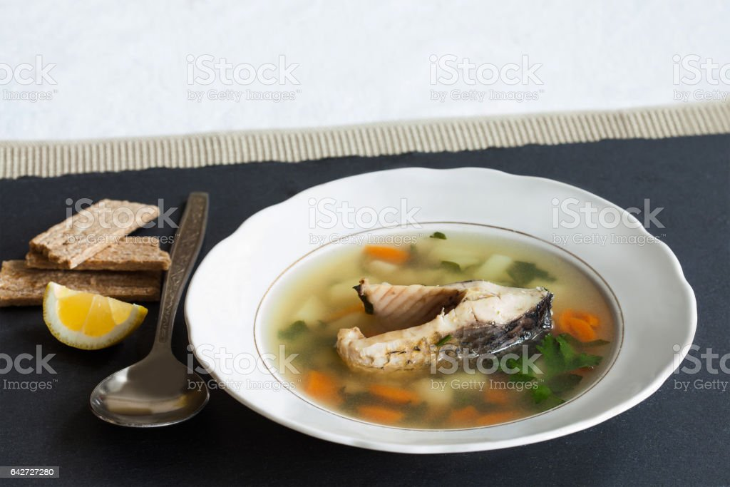 Fish soup on black stone background. Vintage white plate with sliced fish, potato, carrot and herbs. slice lemon, aged spoon, bread stock photo