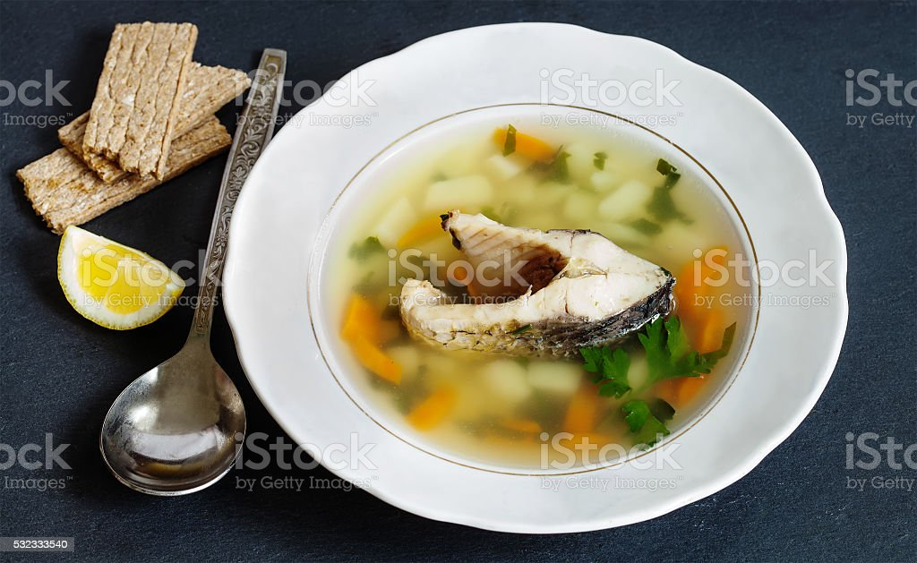 fish soup with vegetables. sliced carp, potatoes, carrot, herbs. copy stock photo
