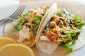Fish Tacos Sit on a White Plate with Lemon Wedges