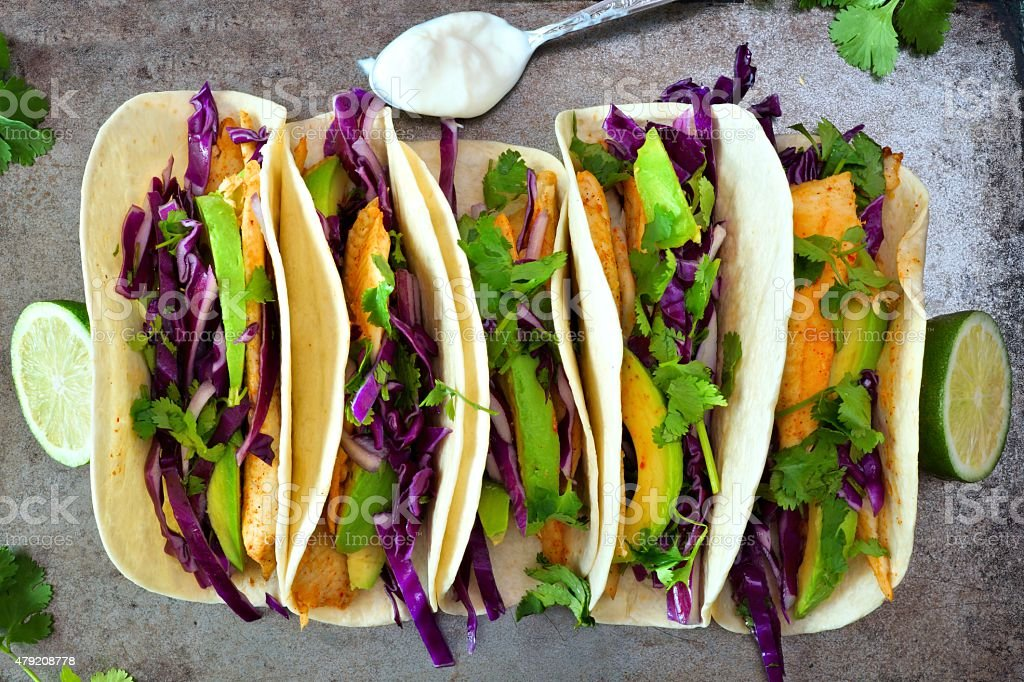 Fish tacos with red cabbage lime slaw on rustic tray stock photo