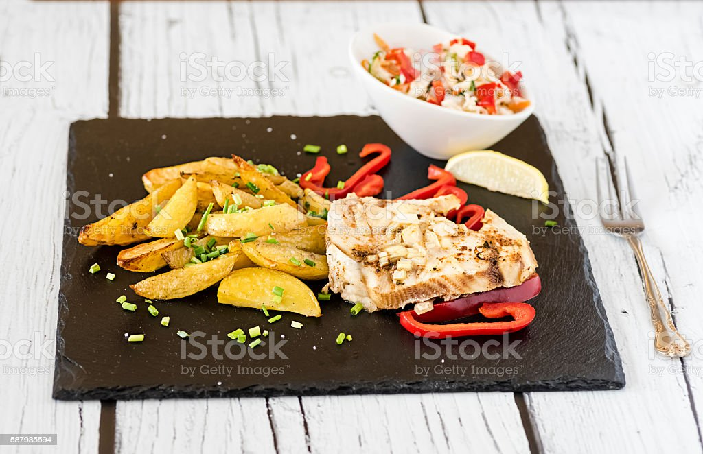 fish with baked potatoes stock photo