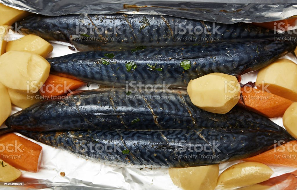 Fish with potato and carrot ready to be cooked stock photo