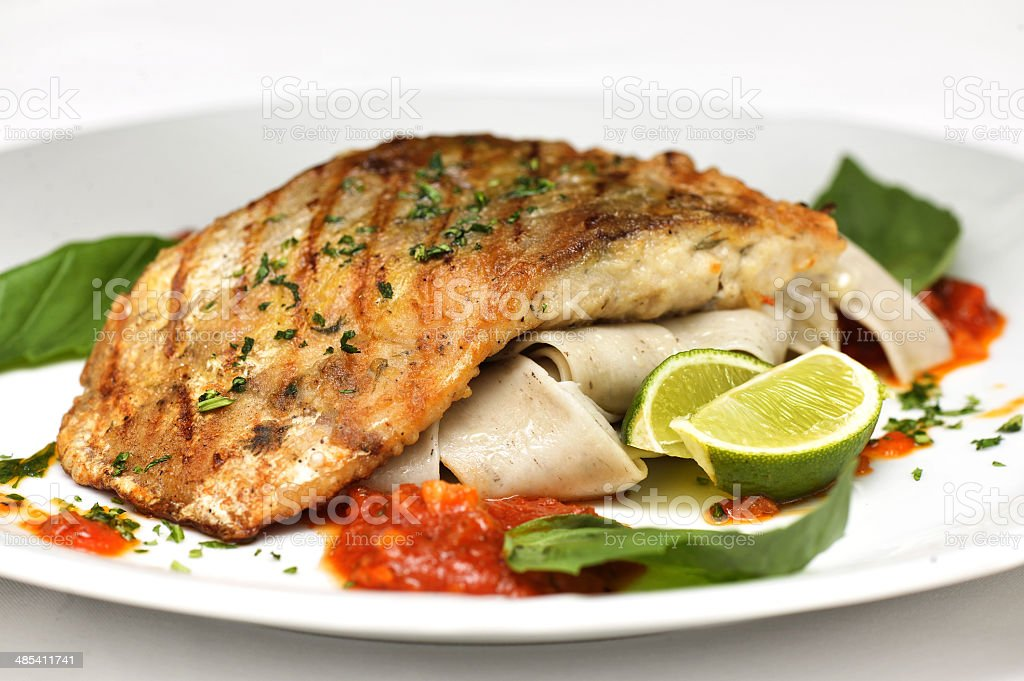 Fish with sauce and greens stock photo