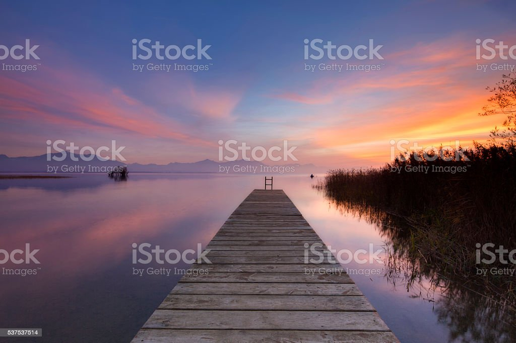 Fisher in  boat at dusk, Lake Chiemsee stock photo