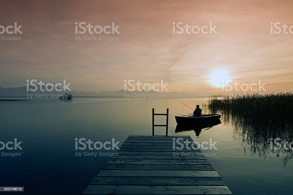 Fisher in  boat at dusk stock photo