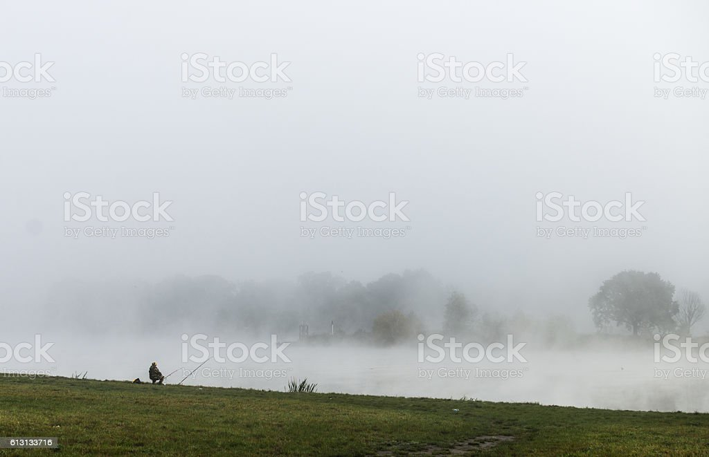 Fisher man fishing  on a river bank at misty sunrise stock photo