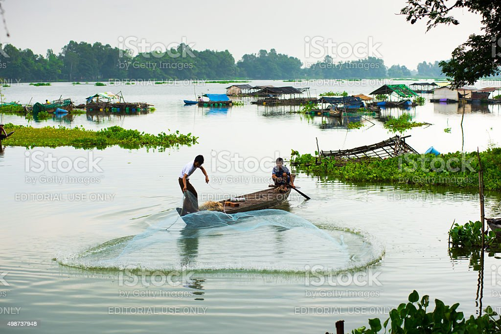 Fisher throws fish net in a lake in An Giang stock photo