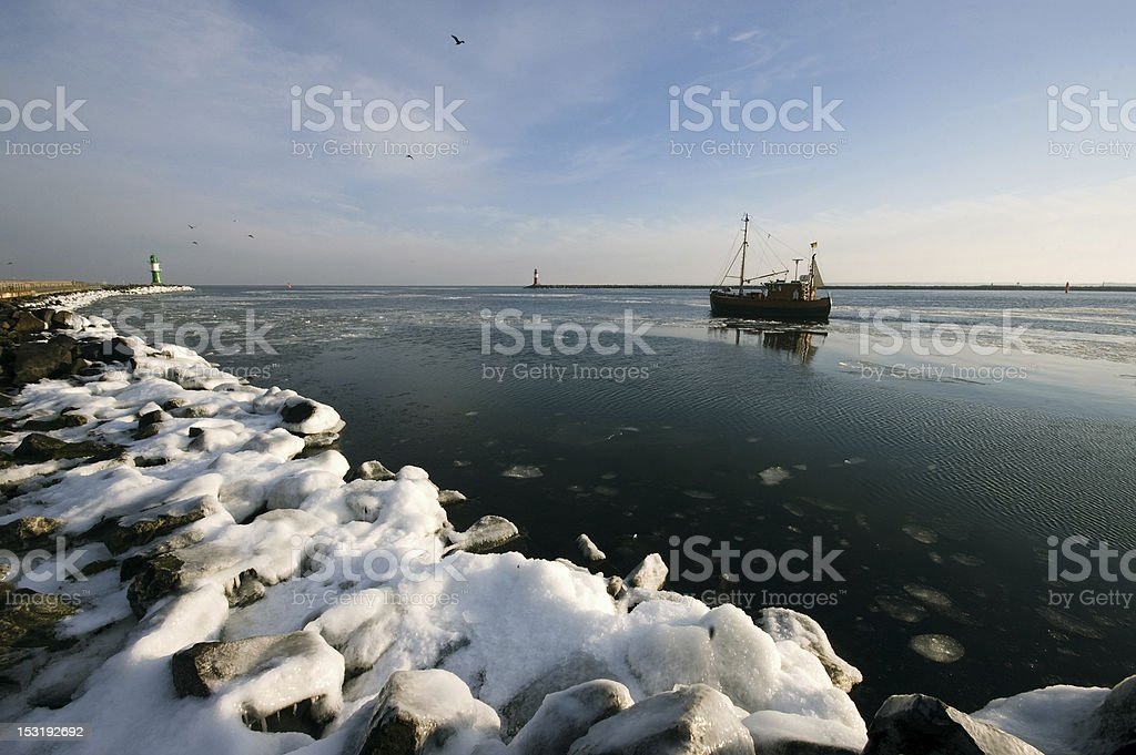 Fisherboat in Wintertime with two lighthouses royalty-free stock photo