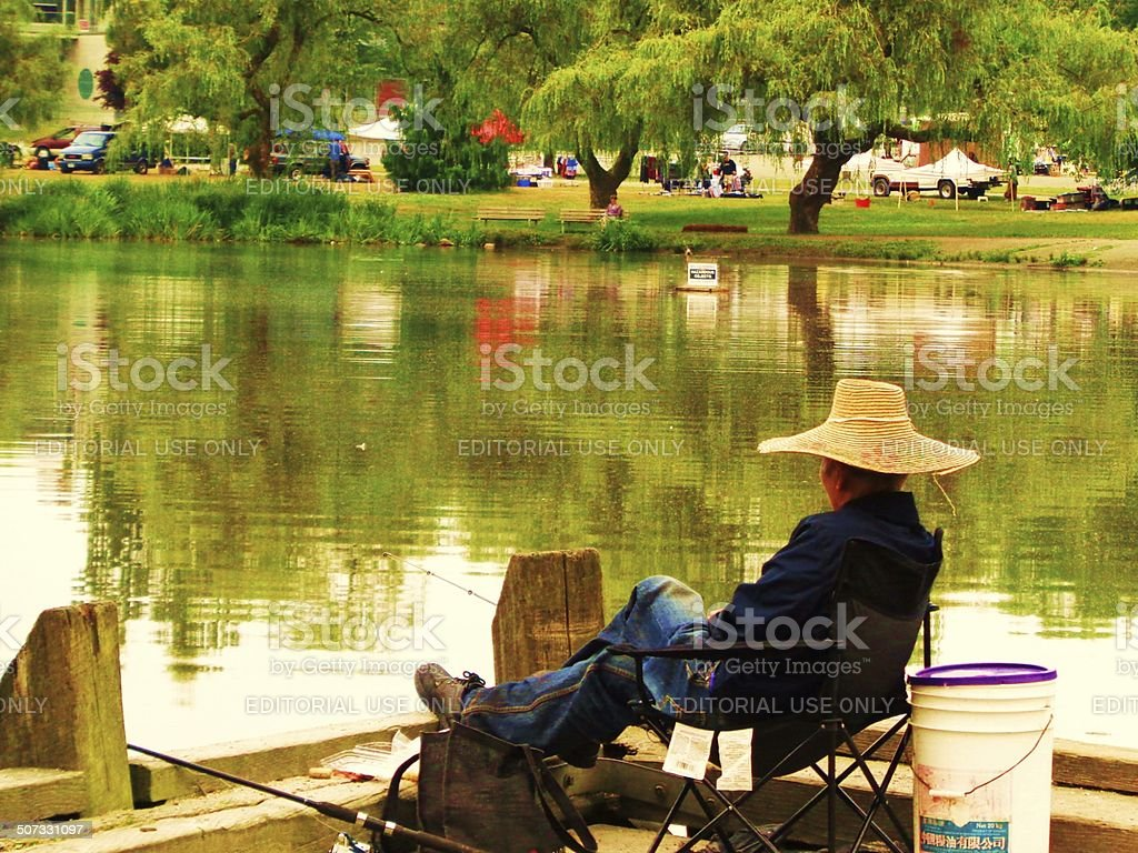 Fisherman across lake from Latin Summer Fest stock photo