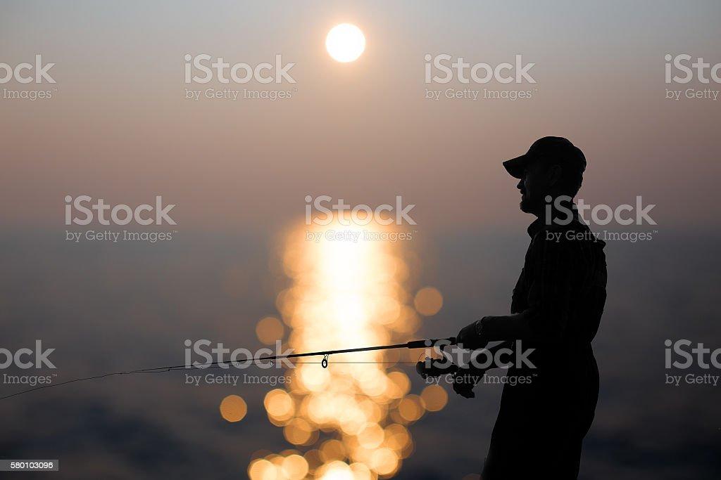 fisherman at dusk stock photo