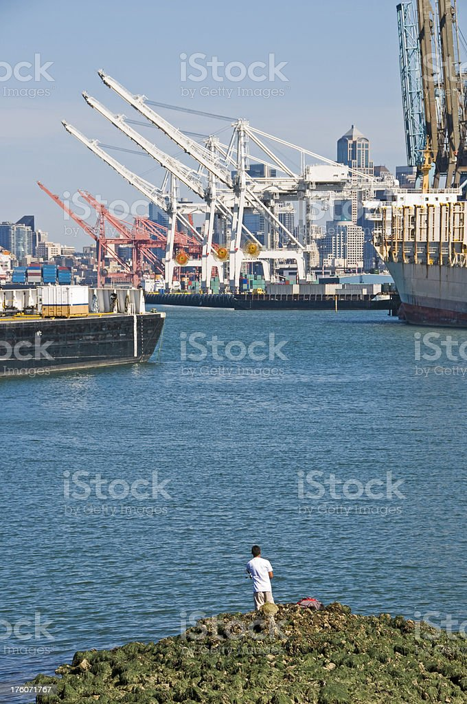 Fisherman at mouth of polluted industrial waterway royalty-free stock photo