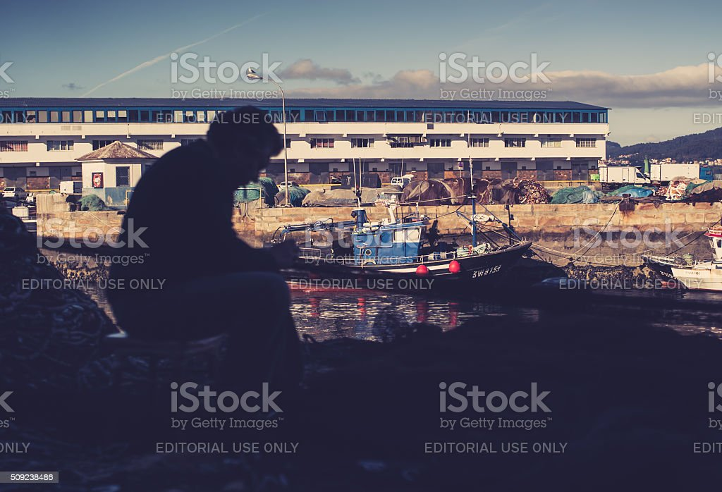 Fisherman at work, cleaning the nets stock photo
