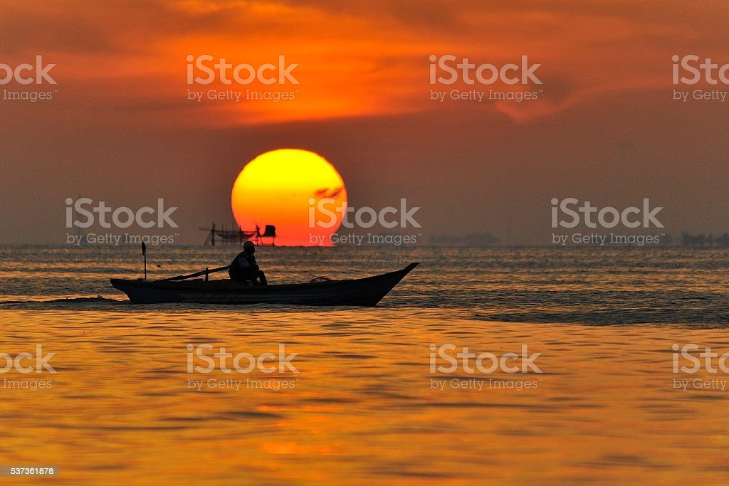 Fisherman boat and sunset stock photo