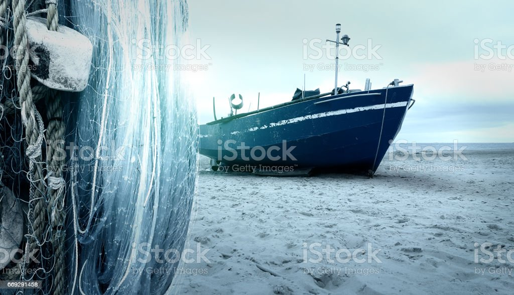 fisherman boat on the ocean beach with sunlight stock photo