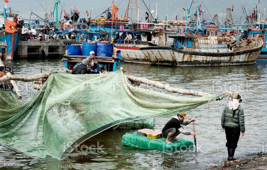 Fisherman bringing baskets with shrimps to the shoreside stock photo