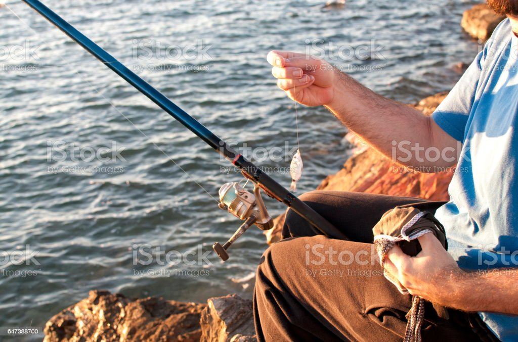Fisherman by the sea at sunset stock photo