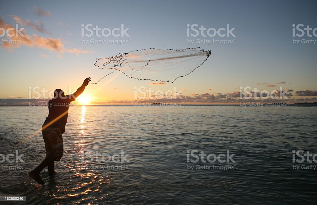 Fisherman casting his net at sunset stock photo