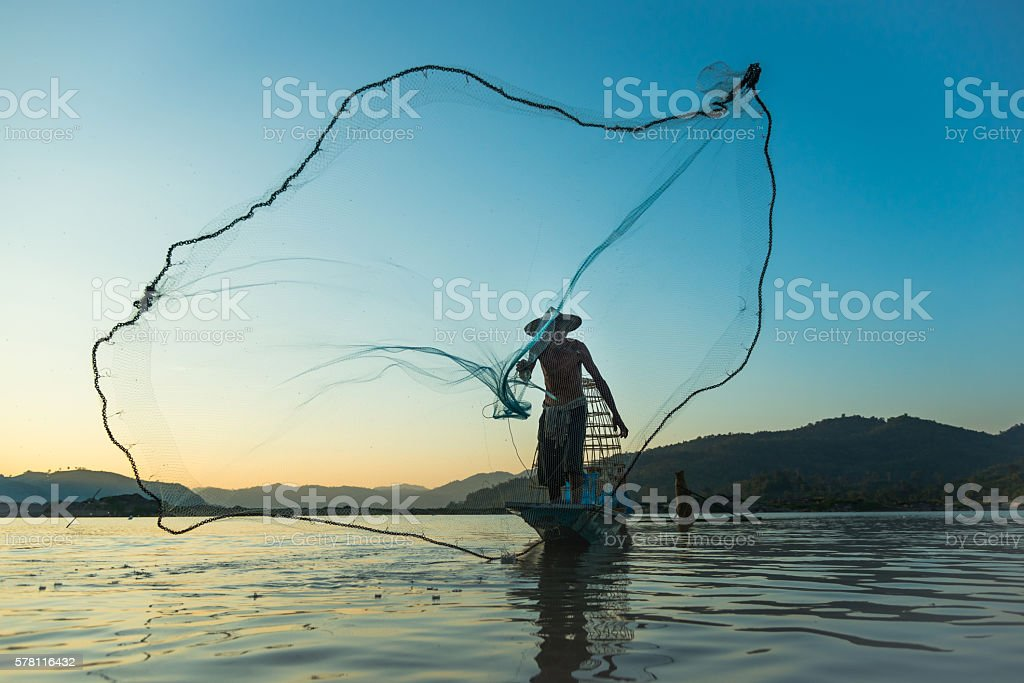 Fisherman casting his net at the sunset stock photo