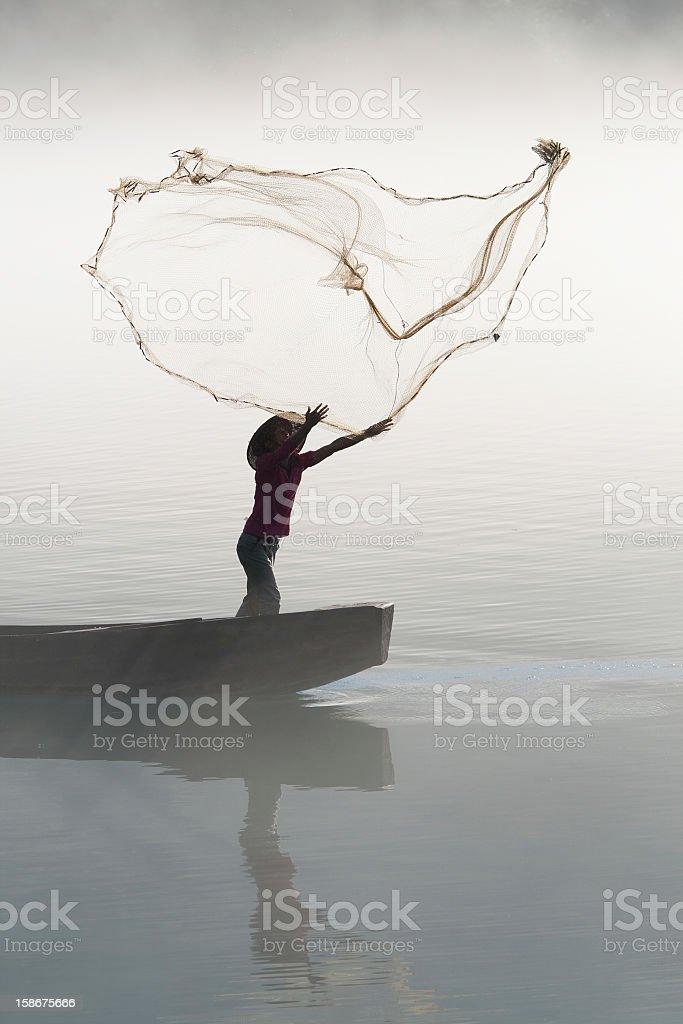 Fisherman casting net on river stock photo