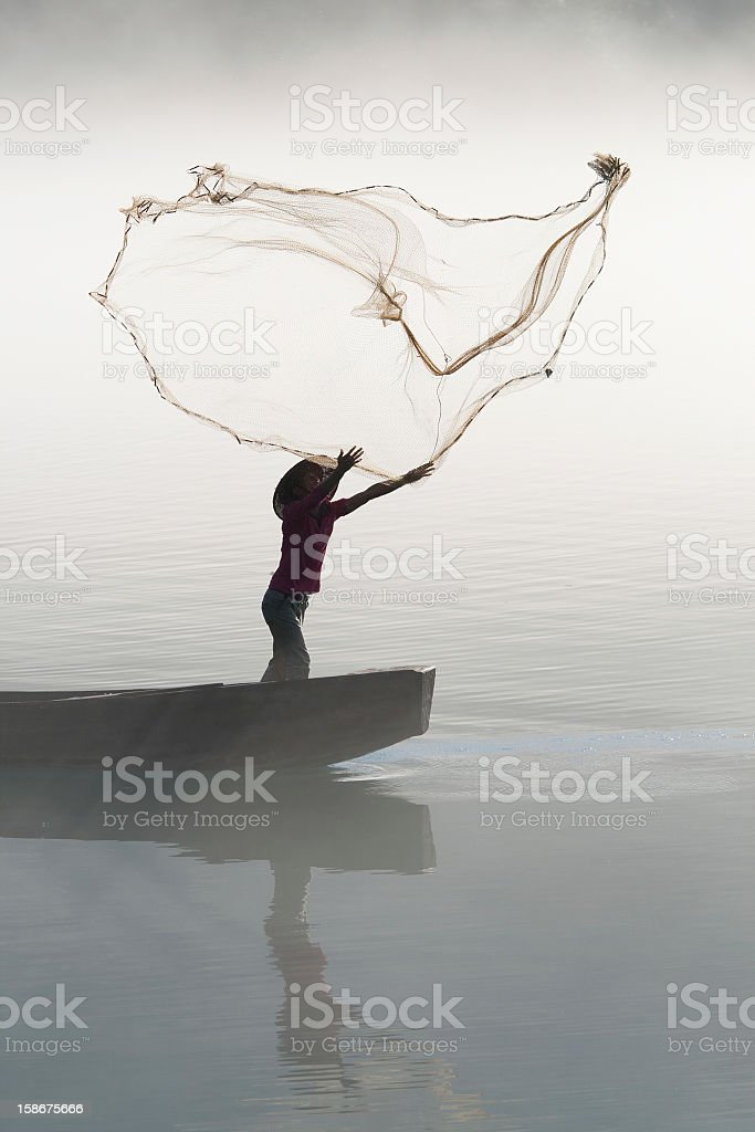 Fisherman casting net on river stock photo